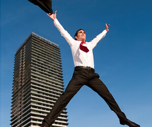 businessman-jumping-in-front-of-office-building